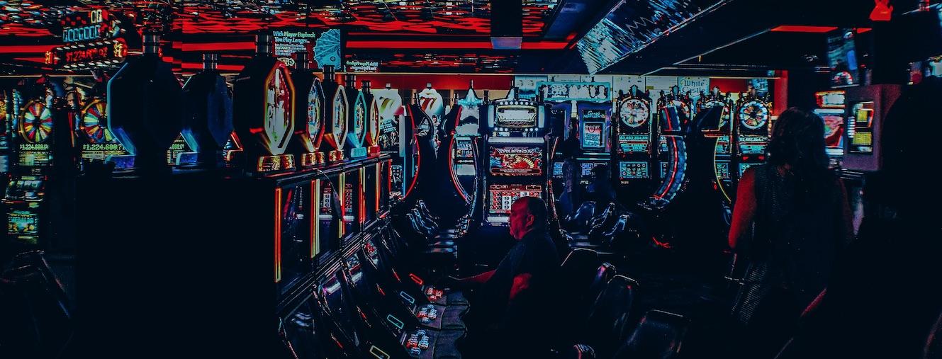 Mand der spiller på spilleautomater i en casino arkade